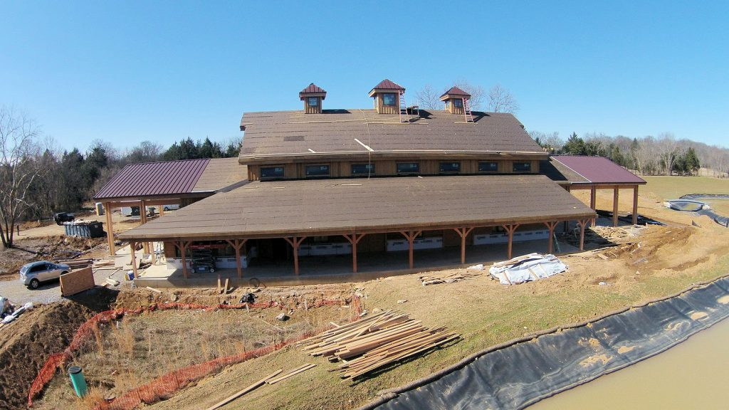 side view of the barn with roof going on